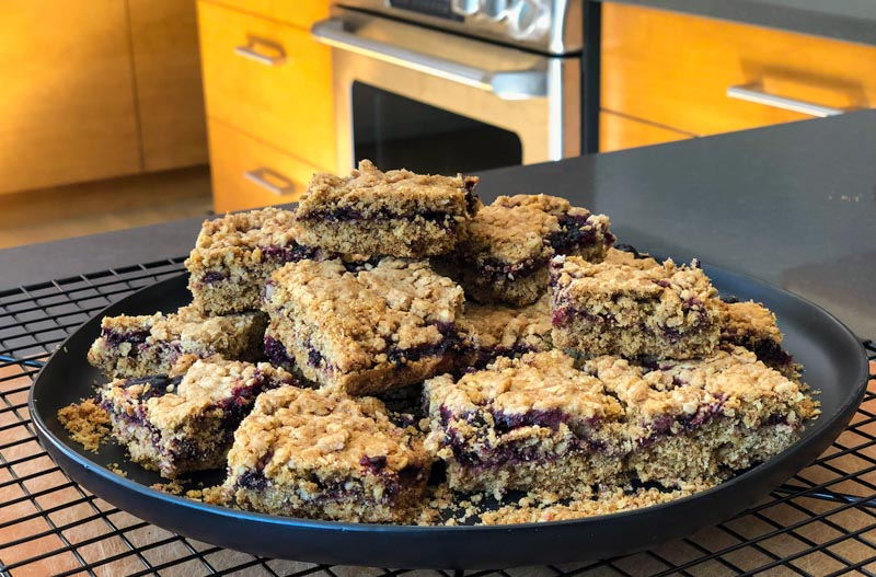 Blackcurrant Jittery Jam Squares, cut and plated with oven in background
