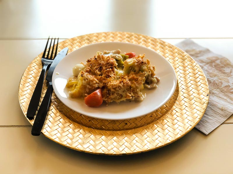 Cooked cauliflower cheese casserole, served on a white plate, gold charger with black utensils`