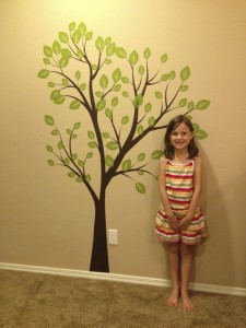 Grace, big sister, in front of the art decal for baby Aaron's room