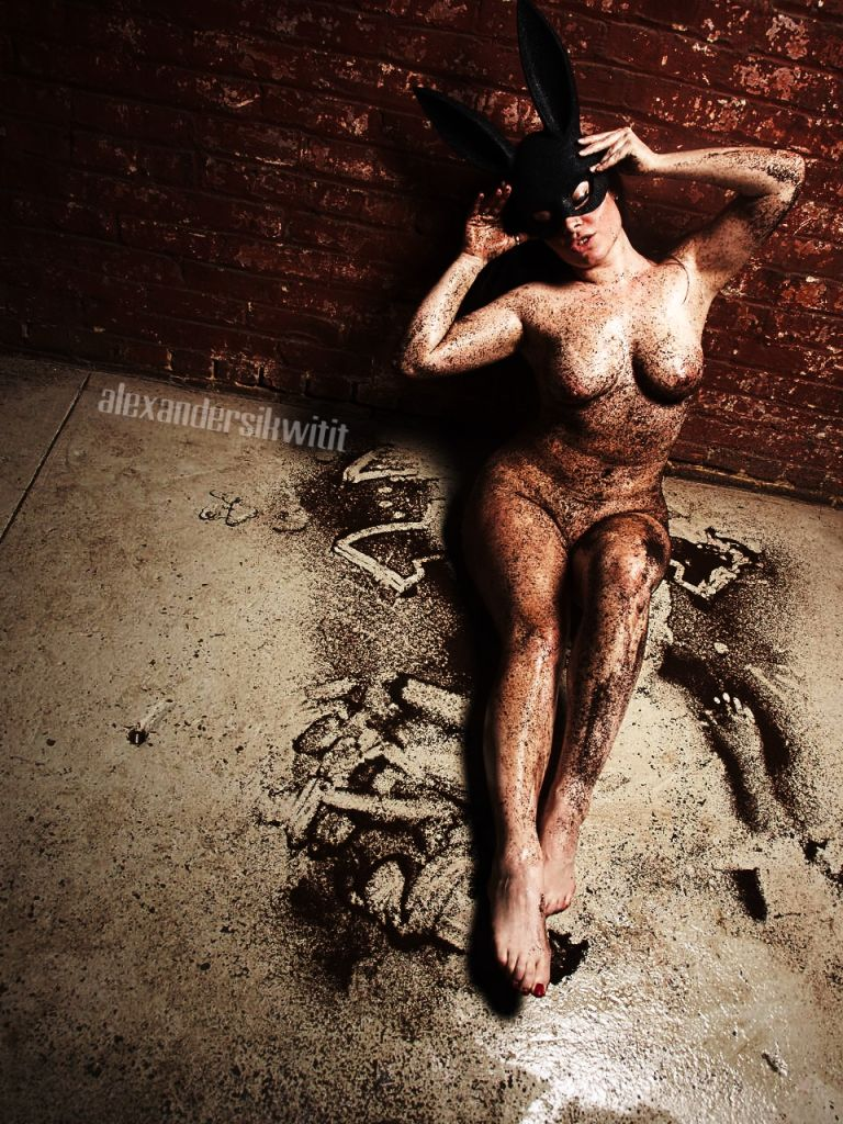 Jasmin sits on a concrete floor, her body covered in coffee grinds wearing a bunny mask sitting up against a red brick wall