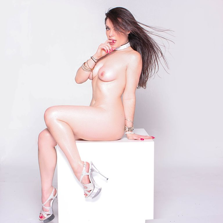 Jasmin Jai sits on a white block with a finger in her mouth