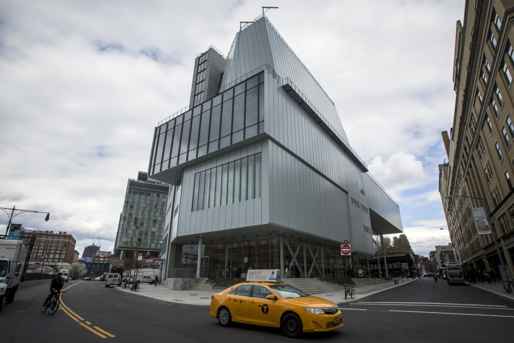 A taxi cab passes by the new Whitney Museum of American Art in New York