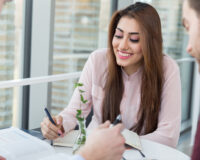 Happy businesswoman planning with male colleagues in meeting