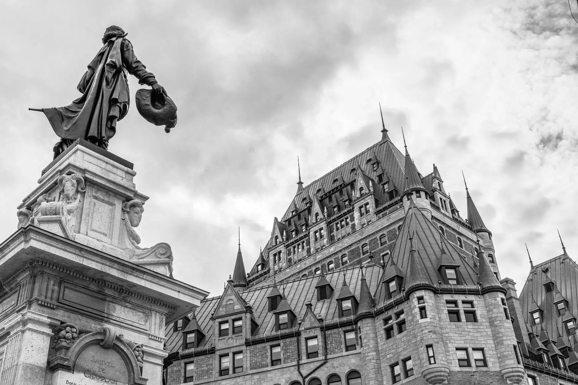grayscale photo of statue of man on top of building