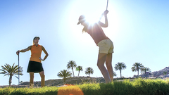 Mature female golfer playing a shot while friend watching her on golf course