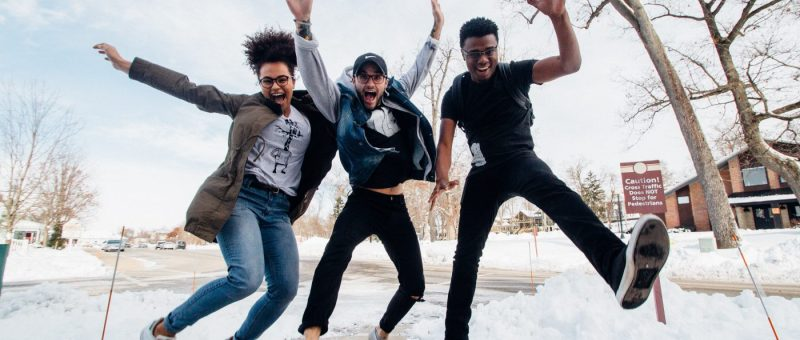 three young people jumping in snowy background