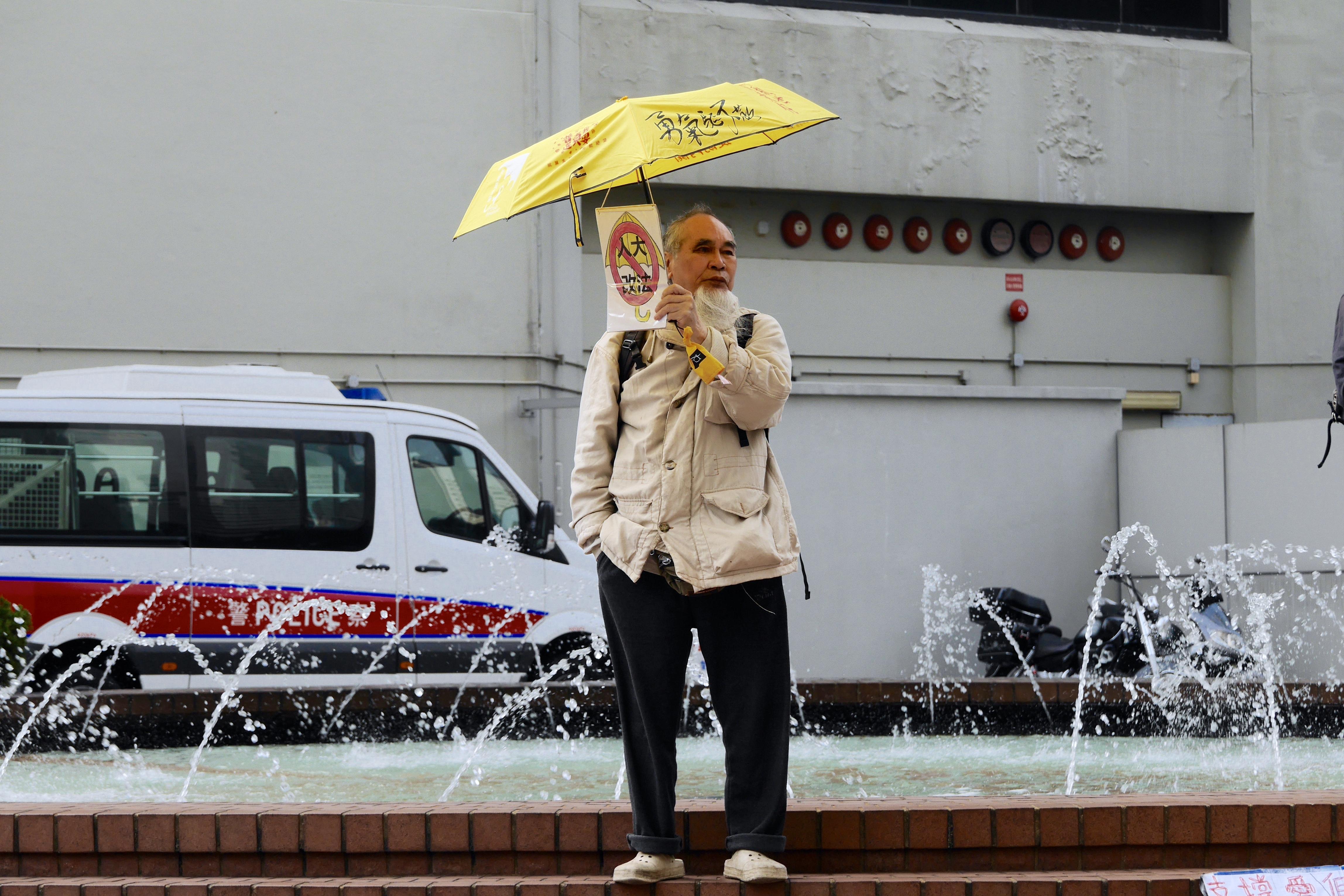 有支持者於法庭外撐起黃傘,聲援4名議員。(李洛婷攝)