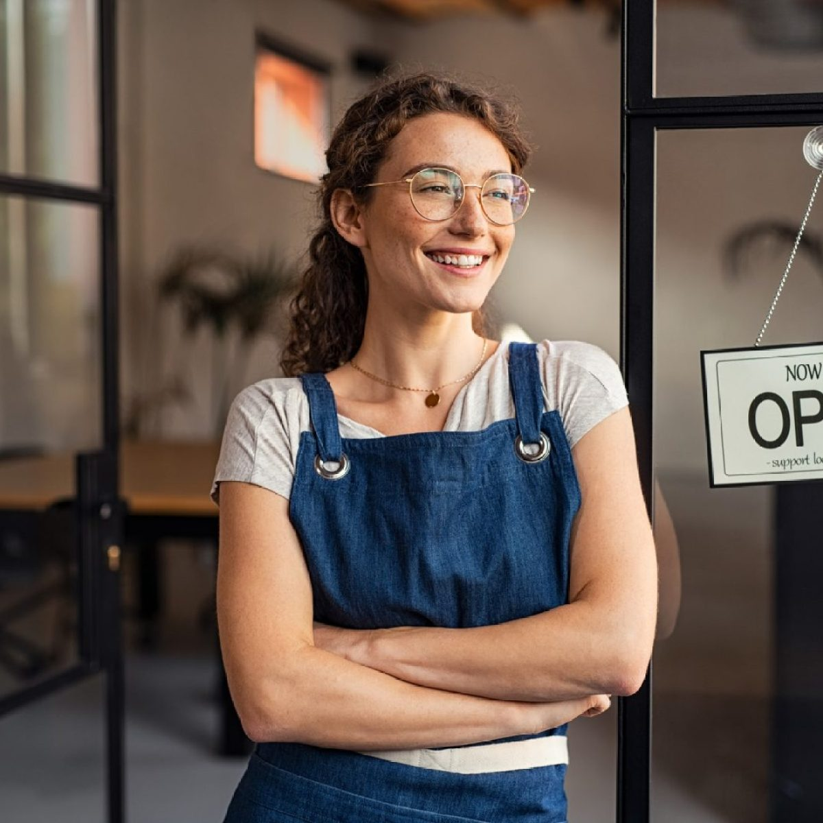 new business start-up owner standing in front of cafe with open sign