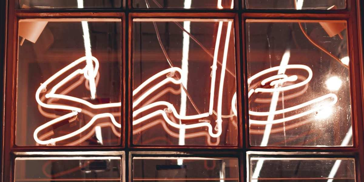 Sale sign in window (neon) - Photo by Alexandre Debiève on Unsplash