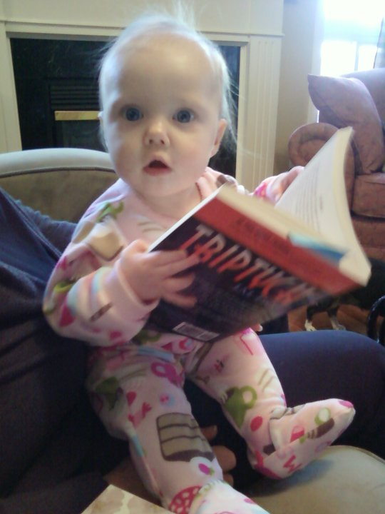 Baby Lila give sthe book a glance; clearly something just happened in teh text that has shocked her.