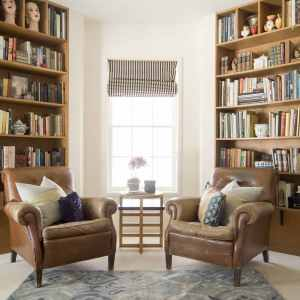 Two leather chairs with bookshelves in the background