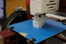 Isabel's model is printing with support material so it doesn't fall over while the printer moves around.