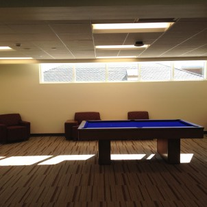 A common room with a pool table and several arm chairs.
