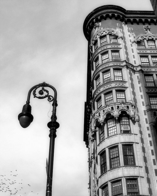 Black and white photo of lamp post and ornate building on NY's East Side, taken by Joana Miranda