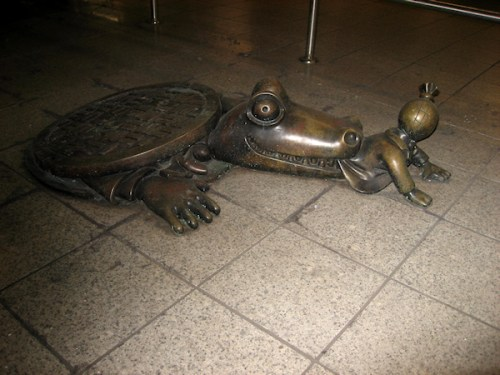 Bronze statue of alligator coming out of man hole to eat a man, taken by Joana Miranda