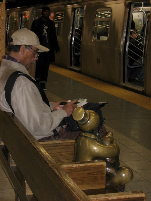 Photo of bronze statue waiting for subway at 14th St. station, taken by Joana Miranda