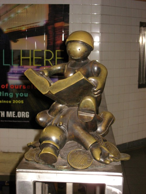 Photo of bronze statue of woman reading a book while seated on top of lifeless man, taken by Joana Miranda