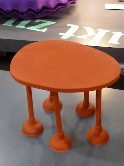 Photo of orange rubber table with plunger legs from the International Contemporary Furniture Fair