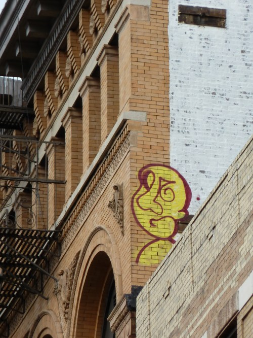 Photo of yellow and red graffiti face on wall in Chinatown, taken by Joana Miranda