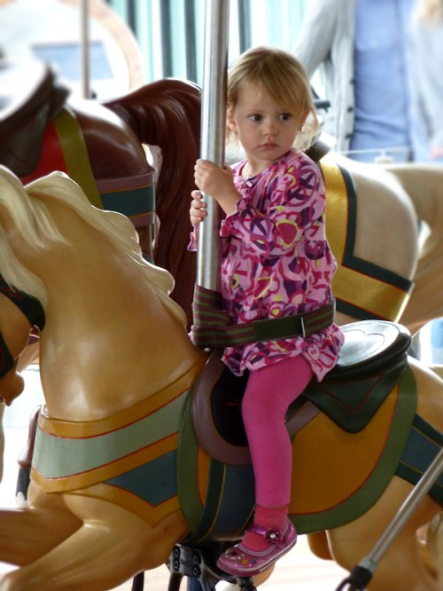 Photo of little girl on carousel horse, taken by Joana Miranda