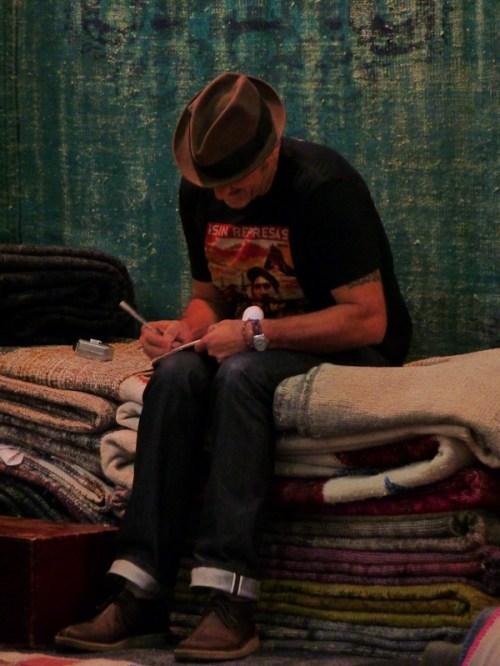 Photo of man sitting on pile of carpets, taken by Joana Miranda