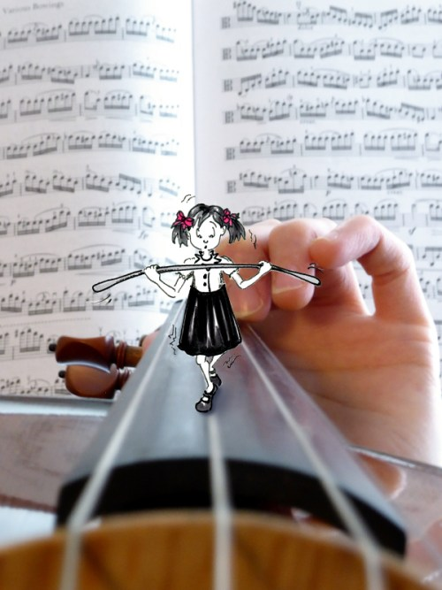 """Photograph of viola fingerboard and music with little cartoon girl walking the """"tightrope"""" strings, photo and cartoon by Joana Miranda"""