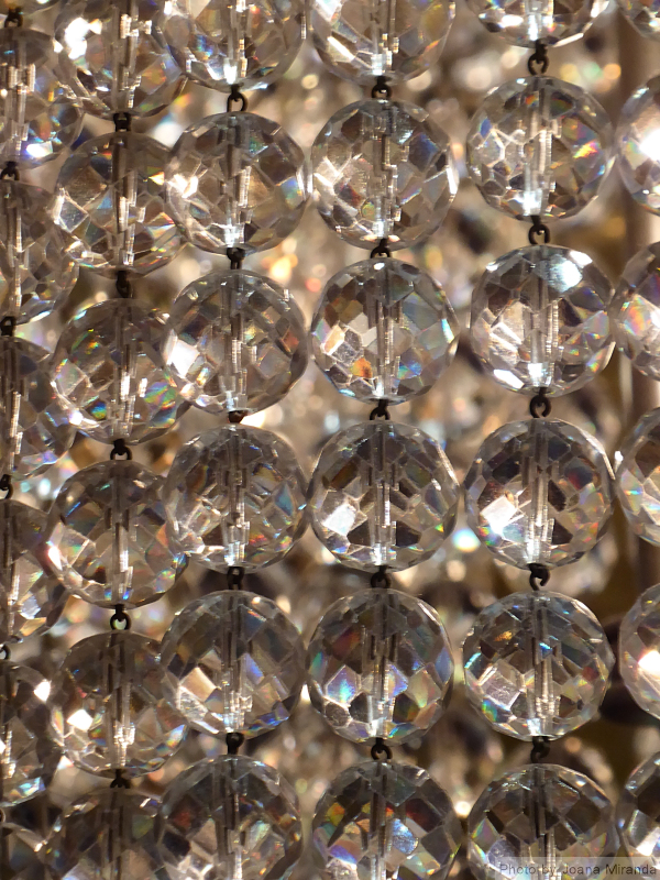 Photo of strings of crystal on a chandelier taken by Joana Miranda