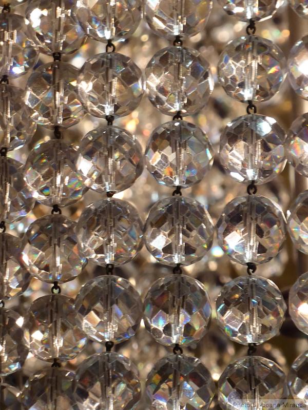 Photo of strings of crystal on a chandelier taken by Joana Miranda