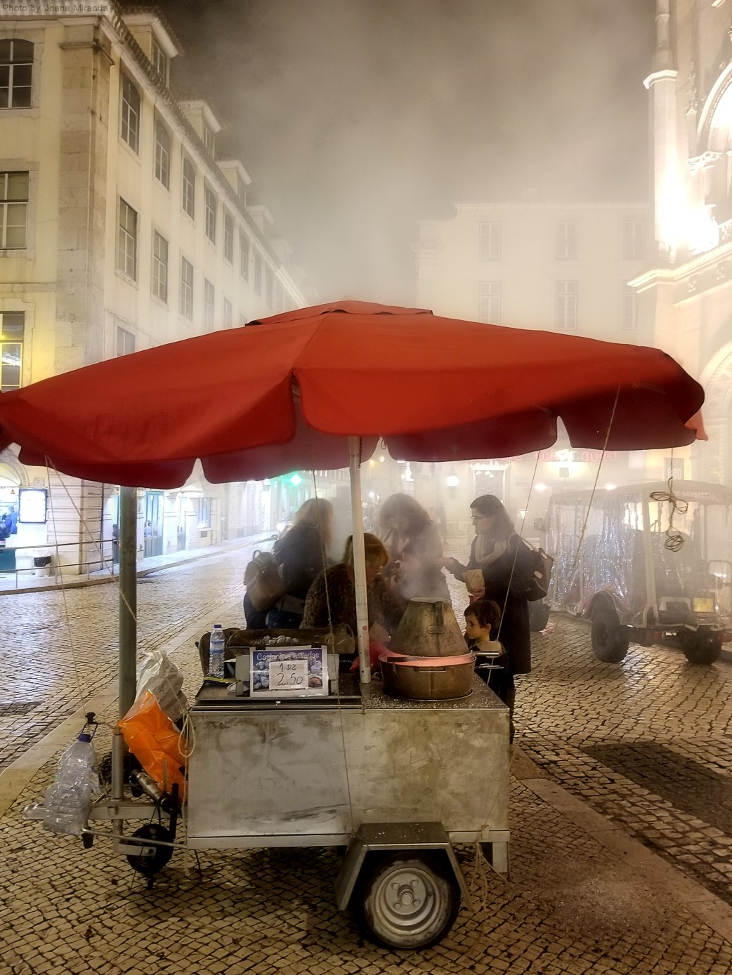 Chestnut vendo stand outside Rossio at night
