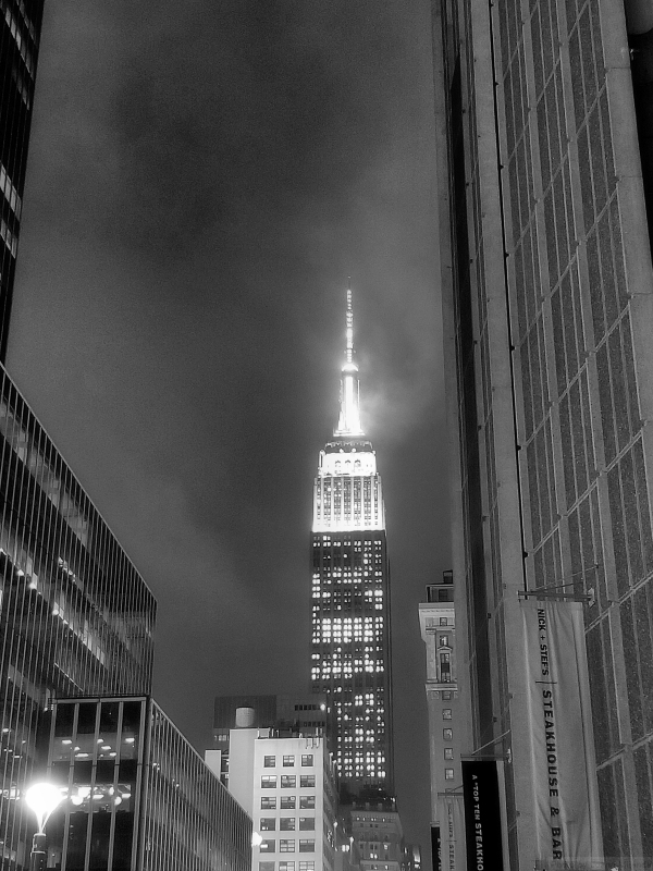 Black and white photo of the Empire State Building at night in the fog, taken by Joana Miranda