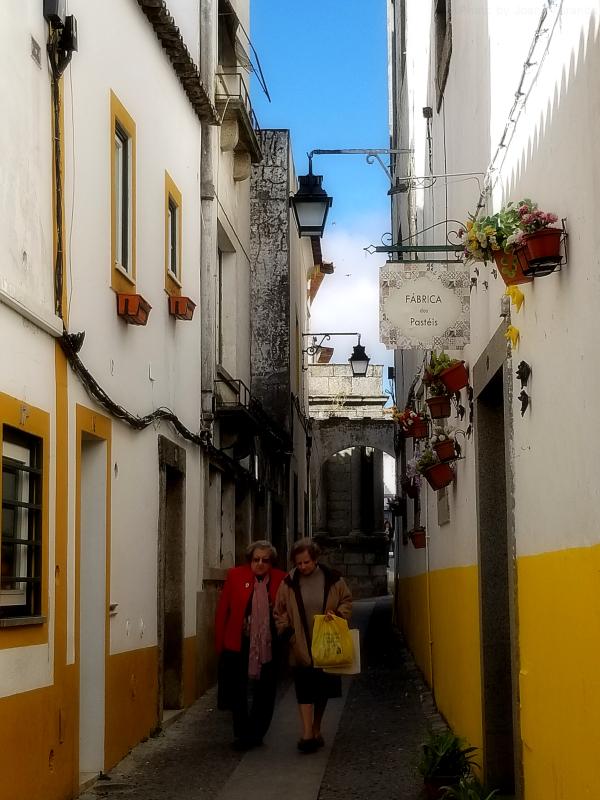 Two Portuguese women walking down a pretty street in Evora, Portugal
