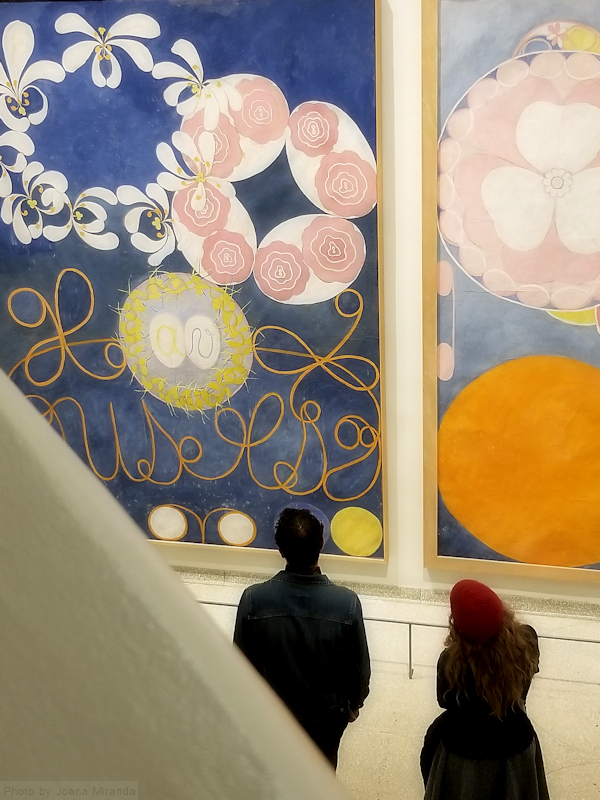 Photo of two patrons admiring the Hilma af Klimt paintins at the Guggenheim Museum, photo by Joana Miranda