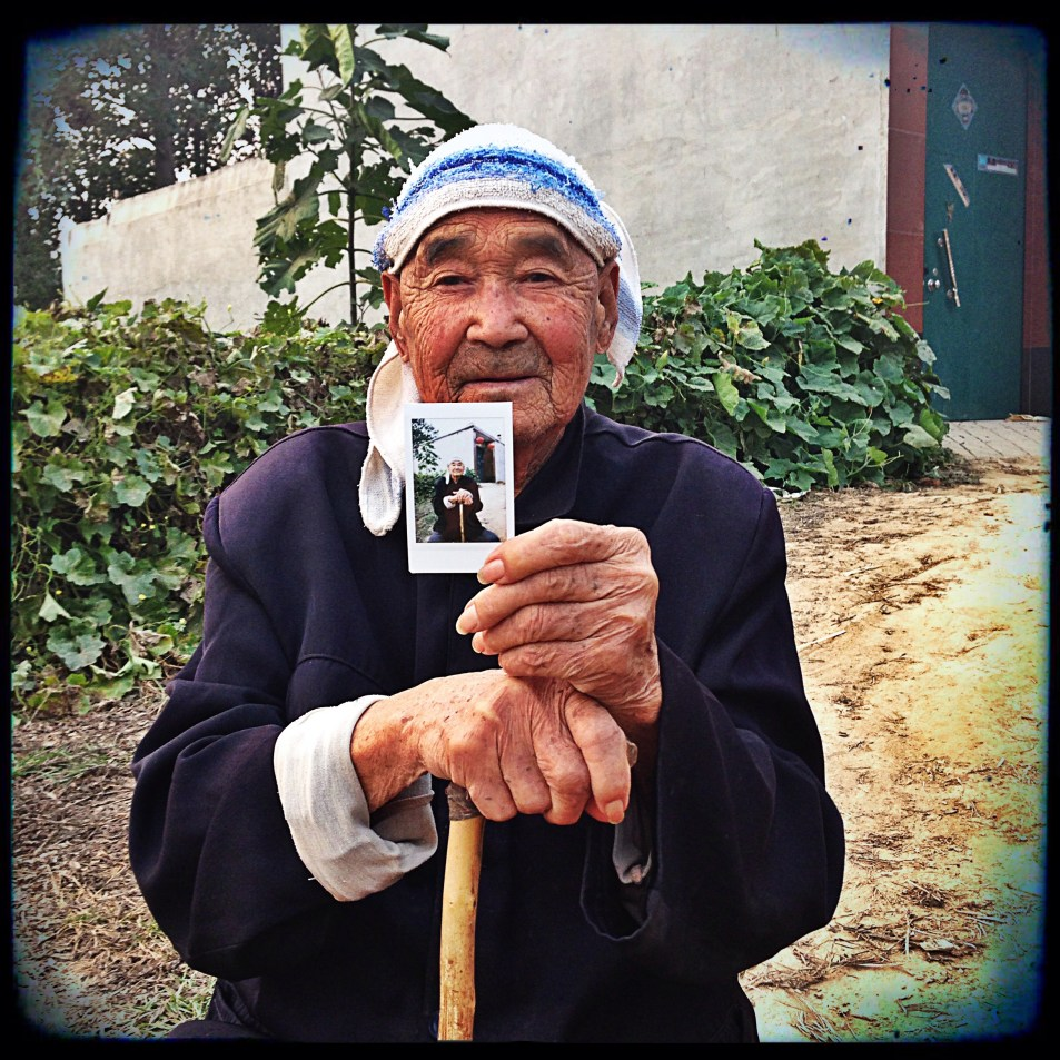Elderly cotton farmer with the first photo of himself he's seen shot by Joanna Bowers while filming in china