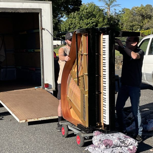 Two men wheel out a black grand piano on a trolley on its side