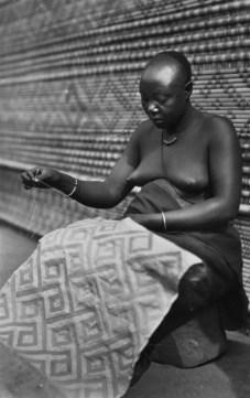 collectie_tropenmuseum_een_bakuba_vrouw_met_scarificaties_op_haar_buik_borduurt_een_mat_congo_tmnr_60033932
