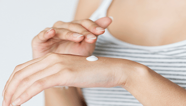 Woman applying topical cream to her hand