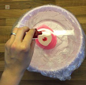 In pinke Plastikschüssel wird Nagellack hineingetropft
