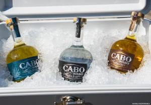 three types of cabo wabo tequila sitting in a cooler of ice