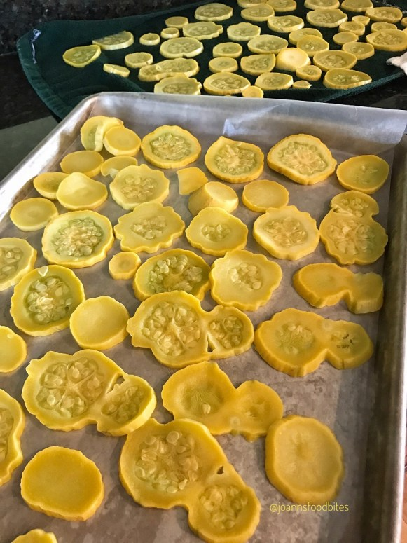 summer squash on a towel and a sheet pan for drying