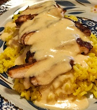 grilled chicken with creamy cheese sauce over yellow rice
