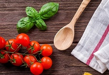 wood background with basil tomatoes and wooden spoon on it