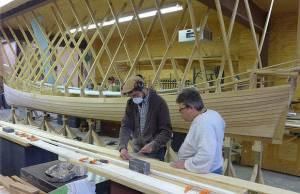 Students Ben Davant, left, and Mike Podgajski shape the final plank for the pilot gig. ((Submitted by Great Lakes Boat Building School))