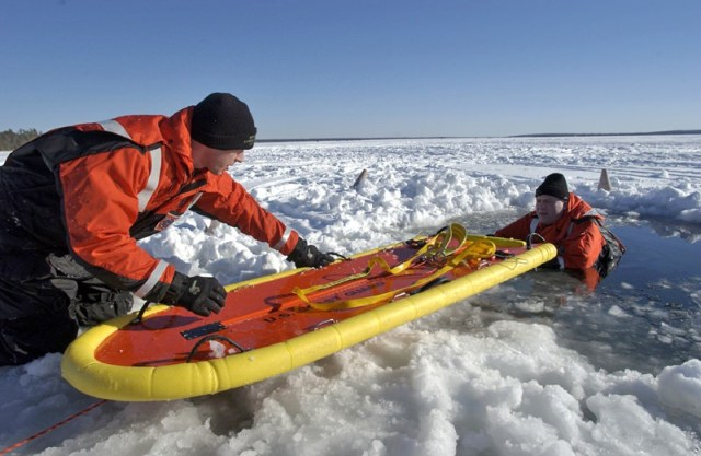 Michigan conservation officers train to perform ice rescue. They learn the proper way to communicate instructions to the victim and how to utilize a rescue board, which disperses the victim's weight across the ice to help prevent further breakage. Here, recruits of a past conservation officer training academy practice these valuable skills./