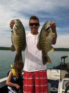 An angler proudly displays his smallmouth bass catch.