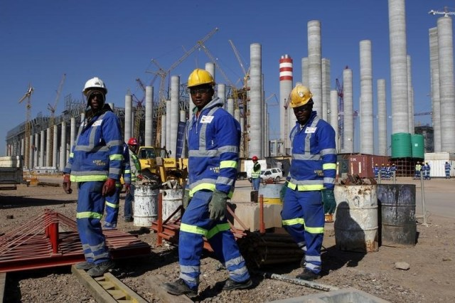 Workers are seen in front the construction site of Eskom's Medupi power station, a new dry-cooled coal fired power station, in Limpopo province