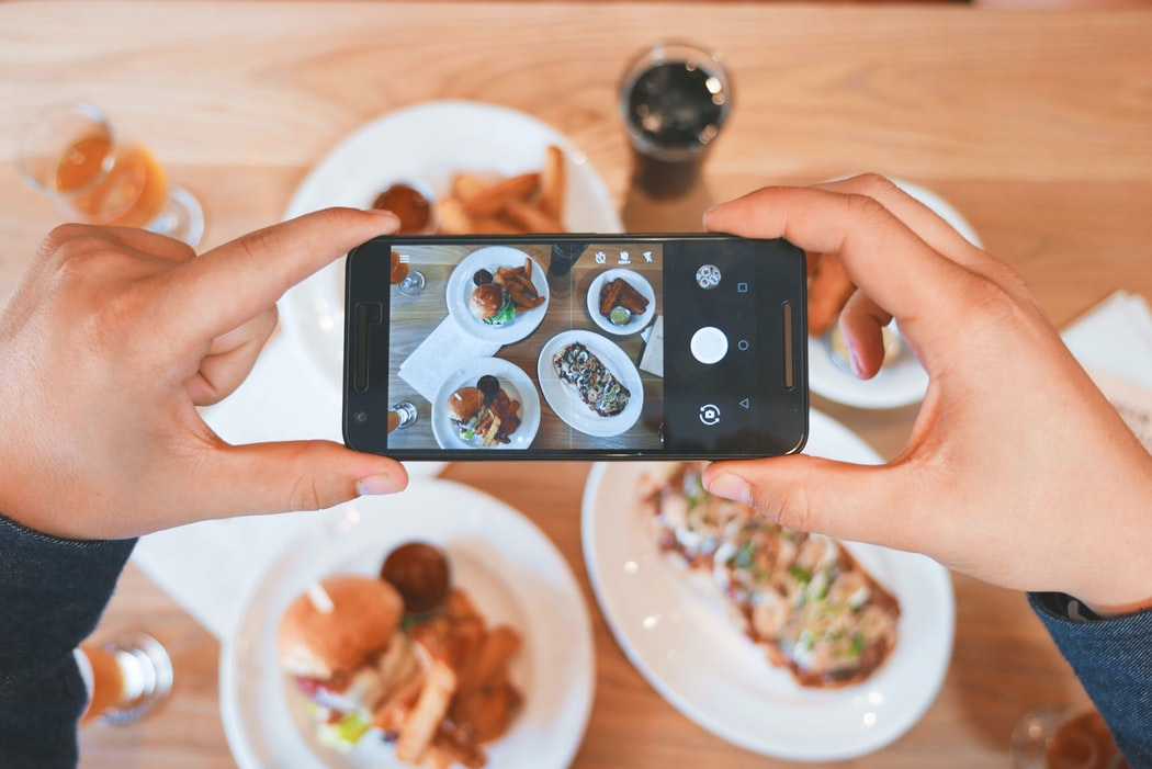 A phone camera taking pictures of dinner plates, perhaps to share on social media.