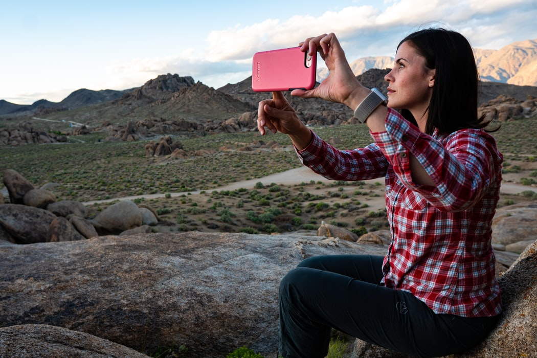 A lady photographs a hilly landscape for her Instagram.