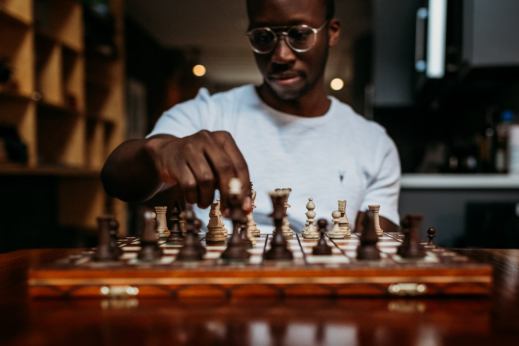 A man in a white shirt plays chess. Winning the classic game involves developing a robust strategy. Likewise, a strong recruitment strategy will help you hire more, high-quality candidates.