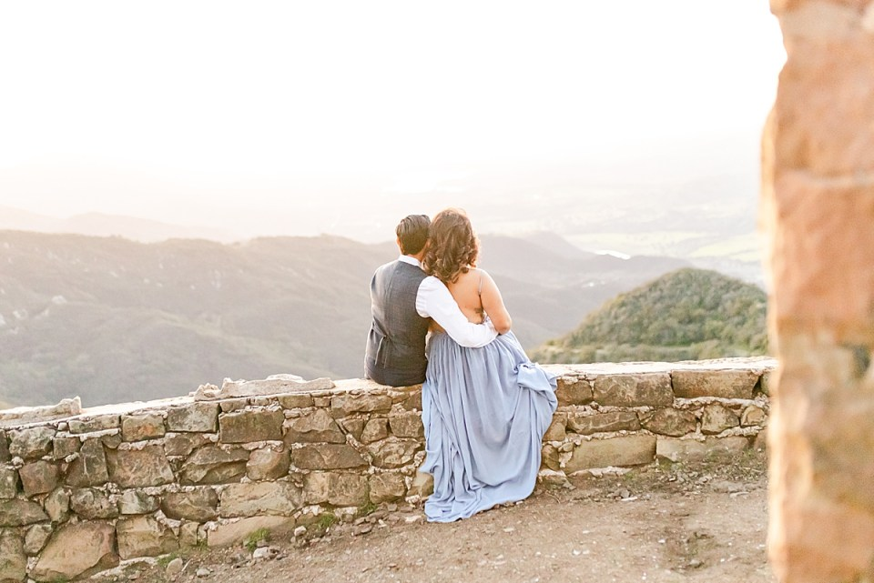 The couple sitting on a rock ledge looking out towards the view from Knapp's Castle.