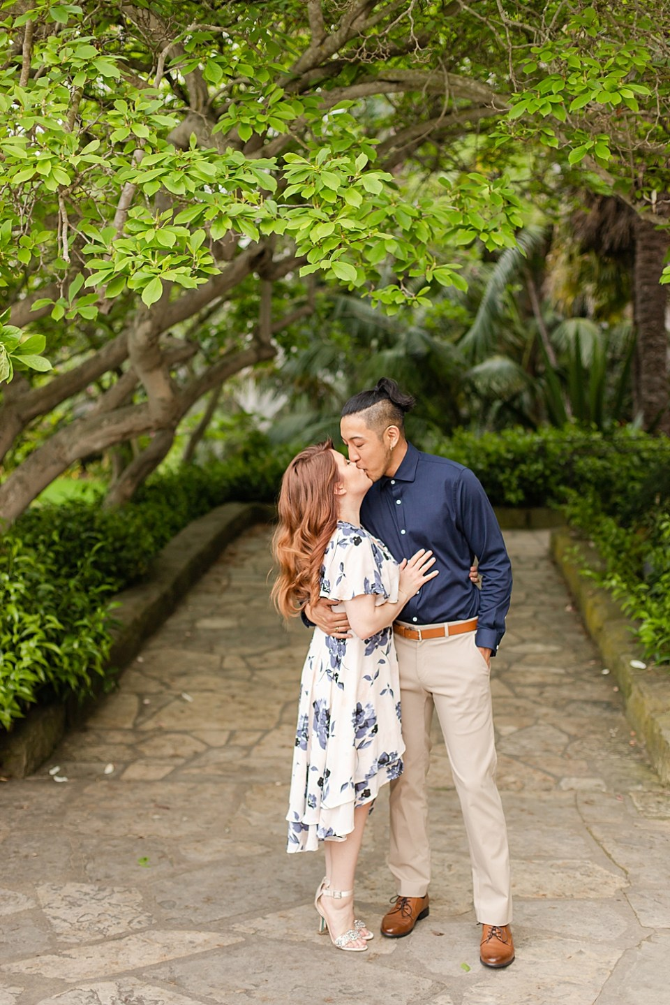 Danielle & Ray under some green trees at the Santa Barbara Courthouse in Santa Barbara, California.